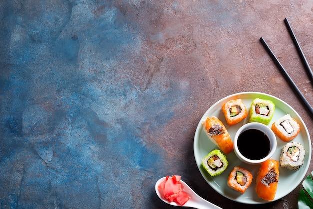 Verschiedene frische und leckere sushi auf keramikplatte mit schieferstangen, sauce auf steinoberfläche