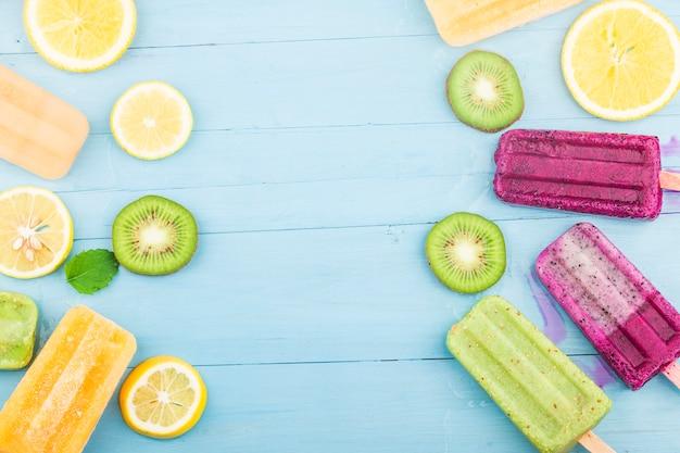 Verschiedene frucht-eis am stiel werden auf den blauen holzbrett-hintergrund gelegt, kiwi-eis am stiel, orange eis am stiel, drachenfrucht-eis am stiel, cantaloupe-eis am stiel