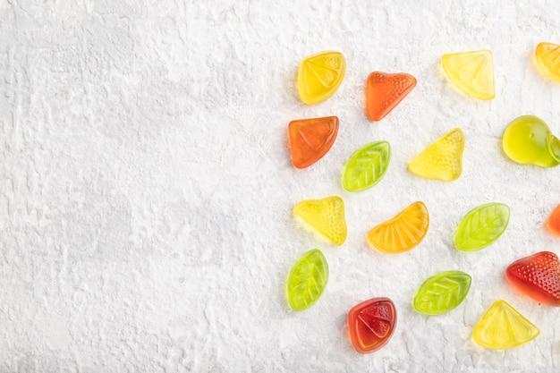 Verschiedene fruchtgelee-bonbons auf grauem betonhintergrund
