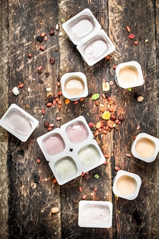 Verschiedene fruchtjoghurts. auf einem hölzernen hintergrund.