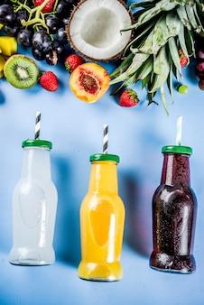 Verschiedene fruchtsäfte smoothies-konzeptsommer-vitamine nähren mit tropischen früchten und beeren auf einem hellen hintergrund
