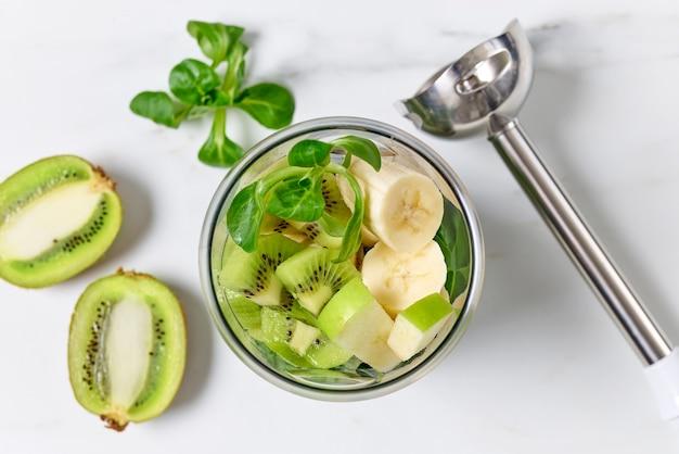 Verschiedene fruchtstücke im mixerbehälter auf küchentisch, selektiver fokus der draufsicht