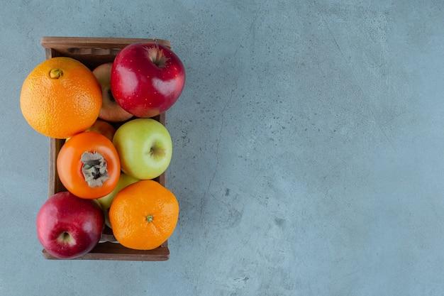 Verschiedene früchte in einer schachtel, auf dem marmorhintergrund. foto in hoher qualität