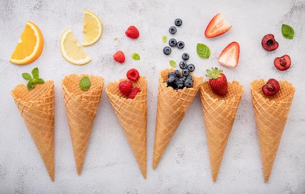 Verschiedene früchte in zapfen heidelbeeren, erdbeeren, himbeeren und erdbeeren auf weißem stein