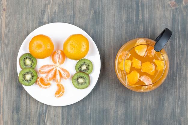 Verschiedene früchte mit einem glas saft in scheiben schneiden