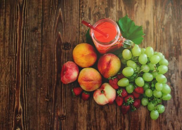 Verschiedene früchte mit einem smoothie auf einem holztisch