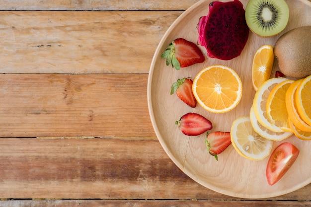Verschiedene früchte mit gemüse auf hölzernem hintergrund