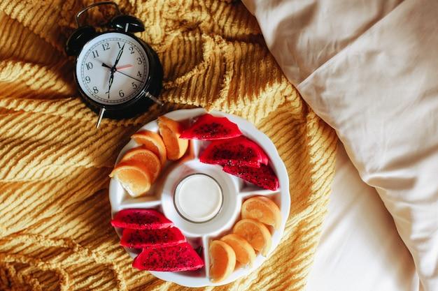 Verschiedene früchte und milch zum frühstück mit uhr auf dem bett 7 uhr