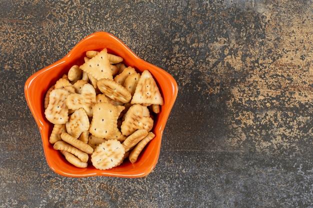 Verschiedene geformte gesalzene cracker in der orangefarbenen schüssel.