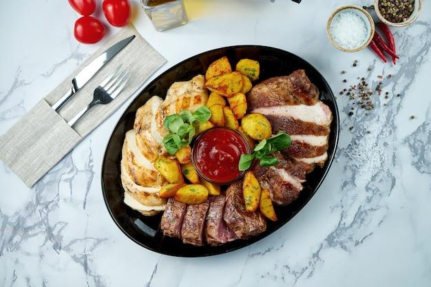 Verschiedene gegrillte fleischsorten, garniert mit kartoffeln mit roter sauce, serviert in einem schwarzen teller auf einer marmoroberfläche
