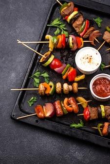 Verschiedene gegrillte kebabs mit fleisch, pilzen, würstchen und gemüse am spieß