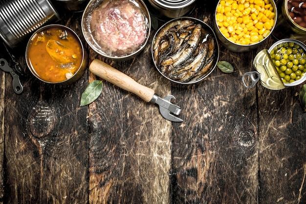 Verschiedene gemüse-, fleisch-, fisch- und obstkonserven in blechdosen. auf einem hölzernen hintergrund.