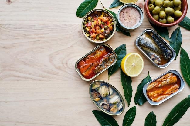 Verschiedene gemüse- und fischkonserven, zitrone und oliven sowie kopierraum. auf holzsockel.
