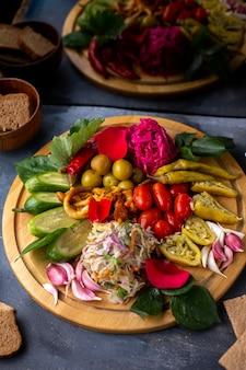 Verschiedene gemüsetomaten oliven mit grünem pfeffer und anderes gemüse auf braunem schreibtisch