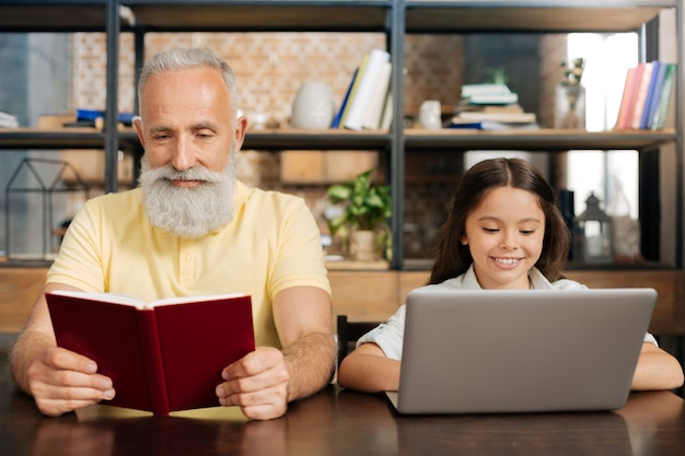 Verschiedene generationen. hübscher älterer mann, der am tisch neben seiner kleinen enkelin sitzt und ein buch liest, während sie ihren laptop benutzt