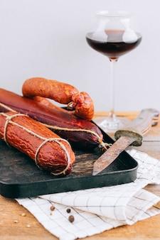 Verschiedene geräucherte würste, vorspeise zu rotwein auf holz