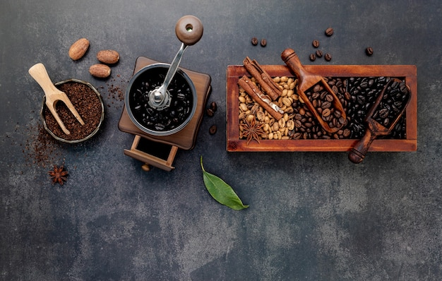Verschiedene geröstete kaffeebohnen in holzkiste mit manueller kaffeemühle auf dunklem stein.