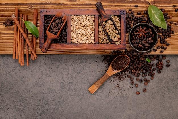 Verschiedene geröstete kaffeebohnen in holzkiste mit manueller kaffeemühle auf schäbigem holz.