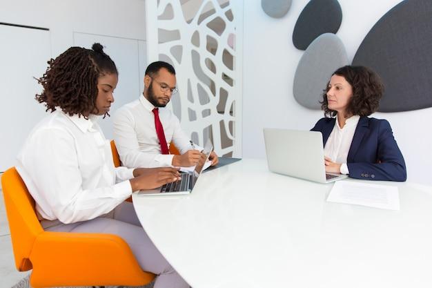 Verschiedene geschäftskollegen, die an weiblichen chef berichten