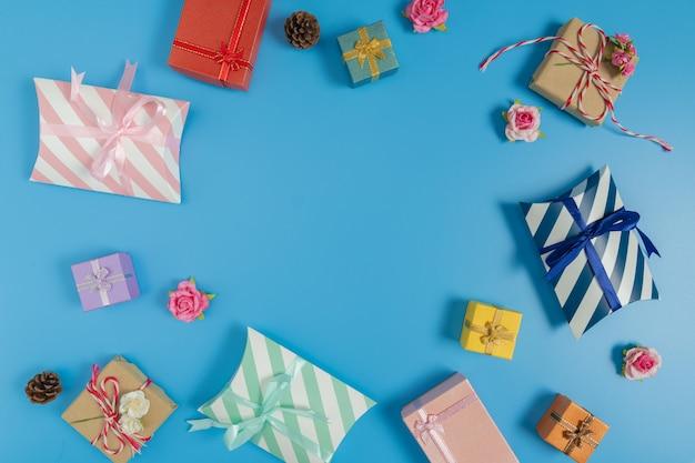 Verschiedene geschenkboxen, kleine rosa rose und tannenzapfen auf blauem hintergrund
