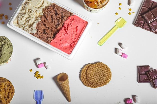 Verschiedene geschmacksrichtungen von handwerklichem eis und waffeln, verziert mit schokoladen- und zuckerwolken.