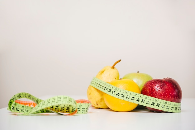 Verschiedene gesunde früchte und messendes band auf tischplatte