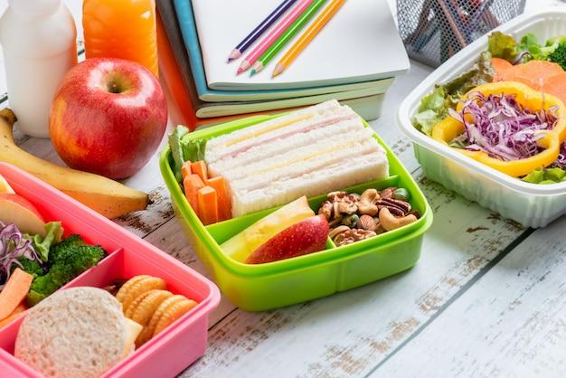 Verschiedene gesunde lunchboxen sandwich. kinder-bento-packung für die schule in plastikverpackung, salatbox, banane und apfel mit orangensaft, milch.