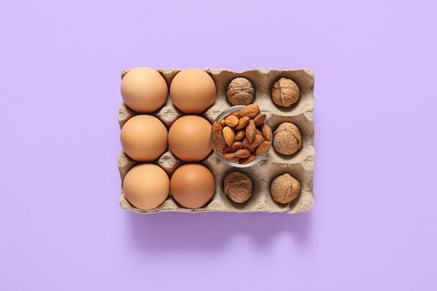 Verschiedene gesunde nüsse und eier auf der farboberfläche