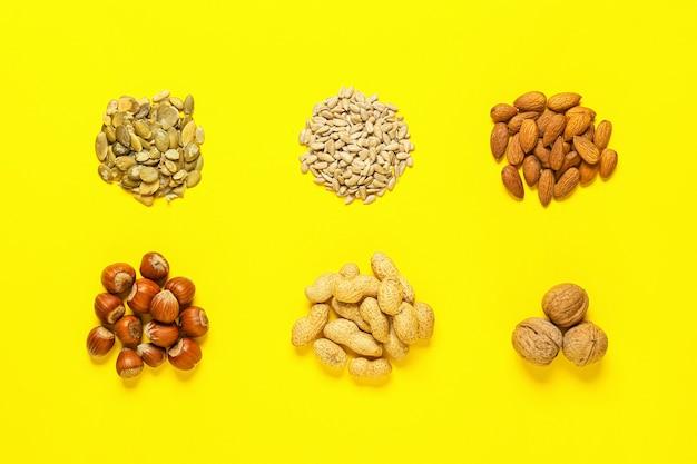 Verschiedene gesunde nüsse und samen auf der farboberfläche