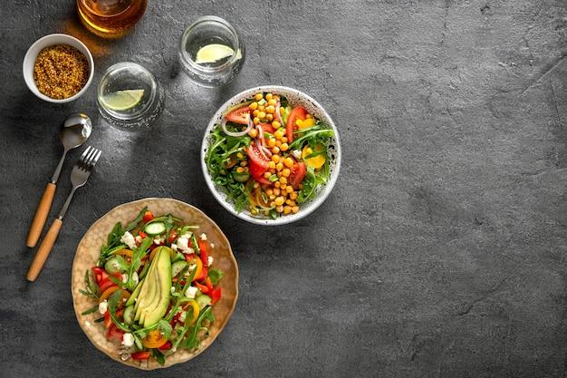 Verschiedene gesunde sommergemüsesalate mit avocado, gurke, rettich, paprika und tomate auf grauem hintergrund. gesundes essen. ansicht von oben.