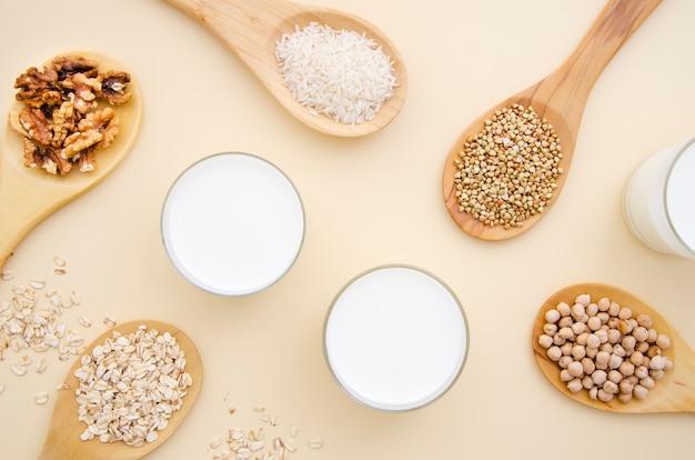 Verschiedene getreide und nüsse in holzlöffeln mit milch
