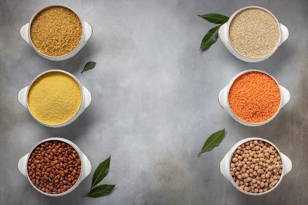 Verschiedene getreidearten: bulgur, couscous, bohnen, quinoa, linsen, kichererbsen, lorbeer. gesundes lebensmittelkonzept. speicherplatz kopieren. graue betonoberfläche, draufsicht
