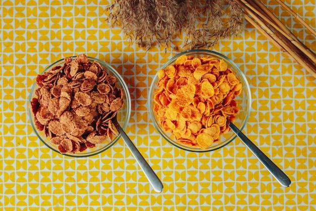 Verschiedene getreidesorten mit löffel in der glasplatte. gesunde ernährung, gesundes essen auf dem tisch mit getrockneten blumen. zwei teller mit unterschiedlichem getreide.