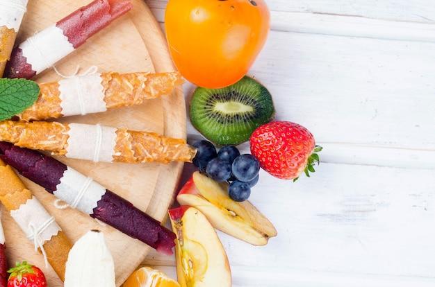 Verschiedene getrocknete chips und reife früchte auf grauem hintergrund. fruchtchips. gesundes ernährungskonzept, snack, kein zucker. ansicht von oben, kopienraum.