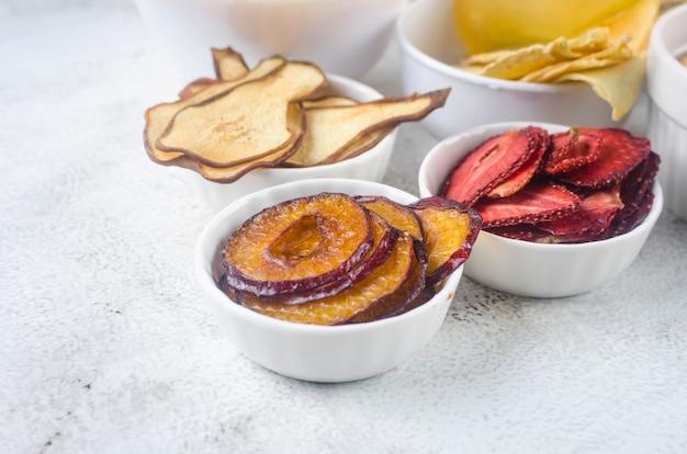 Verschiedene getrocknete chips und reife früchte in platten auf grauem hintergrund. fruchtchips. gesundes ernährungskonzept, snack, kein zucker. ansicht von oben, kopienraum.