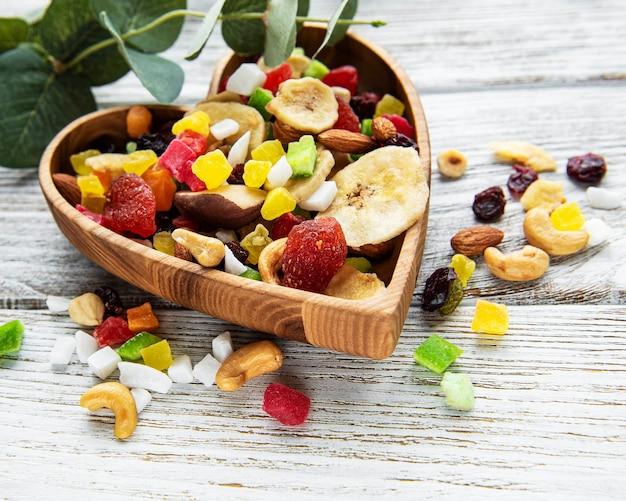 Verschiedene getrocknete früchte und mischungsnüsse auf einem weißen hölzernen hintergrund.