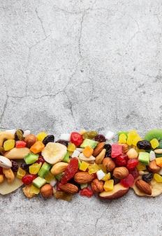 Verschiedene getrocknete früchte und nüsse auf einem grauen betonschreibtisch