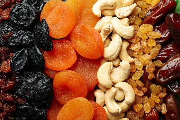 Verschiedene getrocknete früchte und nüsse auf ganzem hintergrund