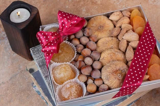 Verschiedene getrocknete früchte und nüsse auf geschenkbox.