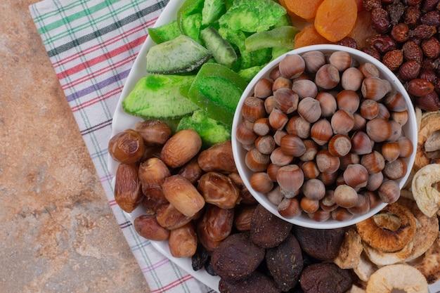 Verschiedene getrocknete früchte und nüsse auf weißem teller.