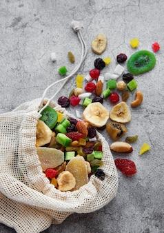 Verschiedene getrocknete früchte und nüsse in einem öko-beutel auf einer grauen betonoberfläche