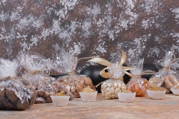 Verschiedene getrocknete früchte und nüsse in plastiktüte und flasche wein verpackt.