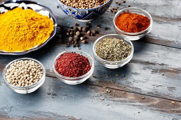 Verschiedene gewürze in schalen auf grauem tisch. paprika, kurkuma, roter pfeffer, kreuzkümmel, koriander. gewürzpulver