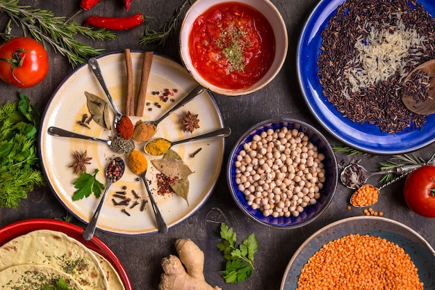 Verschiedene gewürze, kräuter, kichererbsen-, linsen-, basmati- und wildreismischungen, tomatenchutney und pita auf bunten tellern.