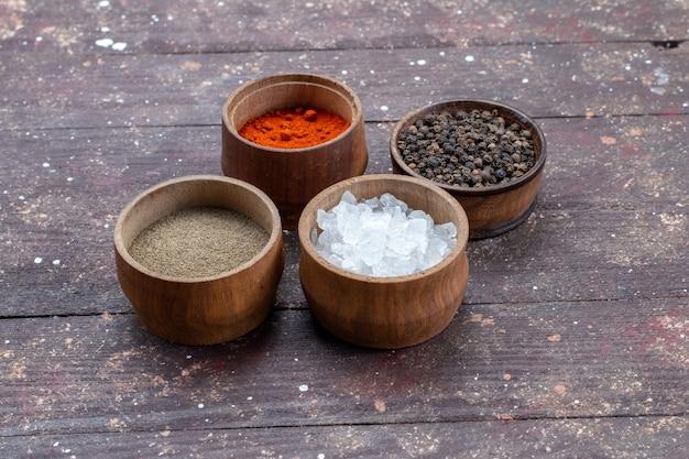 Verschiedene gewürze salz pfeffer in braunen schalen auf braun