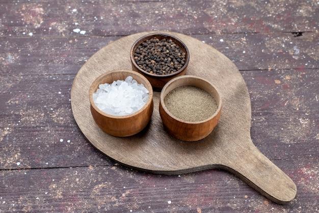 Verschiedene gewürze salz pfeffer in braunen schalen auf braunem rustikalem holzschreibtisch
