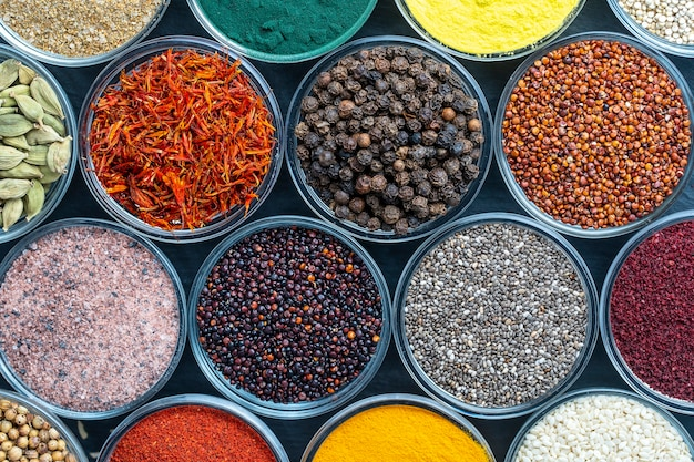 Verschiedene gewürze und kräuter im hintergrund, nahaufnahme, ansicht von oben. sortiment bunte gewürze, samen und kräuter zum kochen von speisen