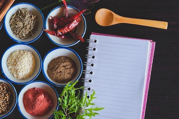 Verschiedene gewürze und kräuter in einer kleinen schüssel mit notizbuch zum kochen von thailändischem essen im hintergrund.