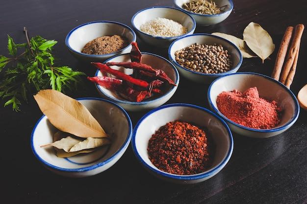 Verschiedene gewürze und kräuter in einer kleinen schüssel zum kochen von thailändischem essen im hintergrund.