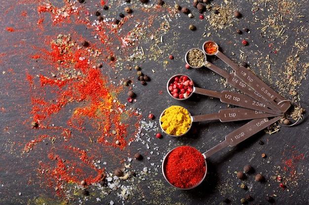 Verschiedene gewürze zum kochen auf dunklem tisch, draufsicht